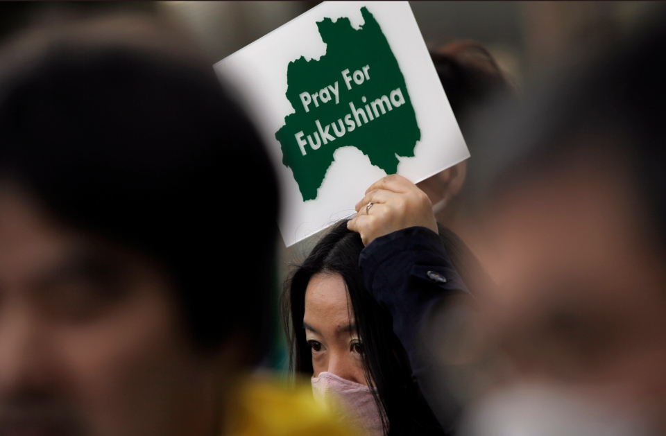 A protester holds a placard to pay tribute to the victims in Fukushima of the March 11, 2011 nuclear disaster following the earthquake and tsunami, during an anti-nuclear demonstration in Tokyo, Saturday, March 9, 2013. (AP / Junji Kurokawa)