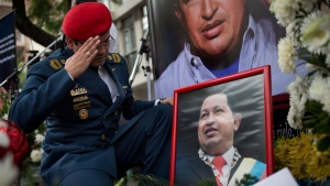 A Venezuelan army officer salutes a photo of Venezuela's late President Hugo Chavez at a makeshift memorial outside the Venezuelan Embassy in Buenos Aires, Argentina on Saturday, March 9, 2013. (AP / Victor R. Caivano)