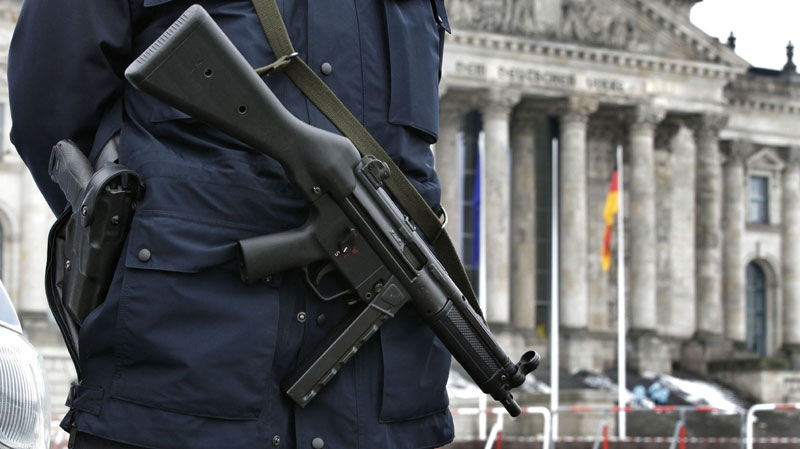 An armed police officer stands guard at the Reichstag building in Berlin, Germany, Friday, Jan. 7, 2011. (AP Photo/Michael Sohn)