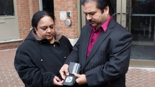 Dinesh Kumar (right) stands with his wife Veena as he displays a photo of their son Gaurov to camera crews as he arrives at the disciplinary hearing for child pathologist Dr. Charles Smith in Toronto on Tuesday February 1, 2011. (Chris Young / THE CANADIAN PRESS)