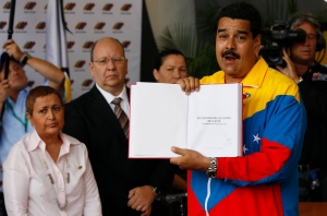 "Venezuela's acting President Nicolas Maduro holds up his government plan titled ""Homeland Program 2013-2019. Commander Hugo Chavez"" after registering his candidacy for president to replace late President Hugo Chavez in Caracas, Venezuela, Monday, March 11, 2013. (AP / Ariana Cubillos)"