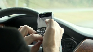 A driver is seen using a cell phone while driving, an illegal offense in most provinces, in this undated photo.