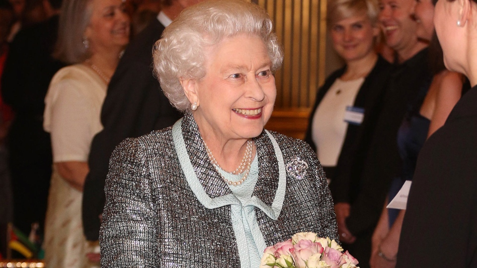 Queen Elizabeth II, head of the Commonwealth, receives a posy at a reception at Marlborough House, London, Monday March 11, 2013. (PA, Philip Toscano)
