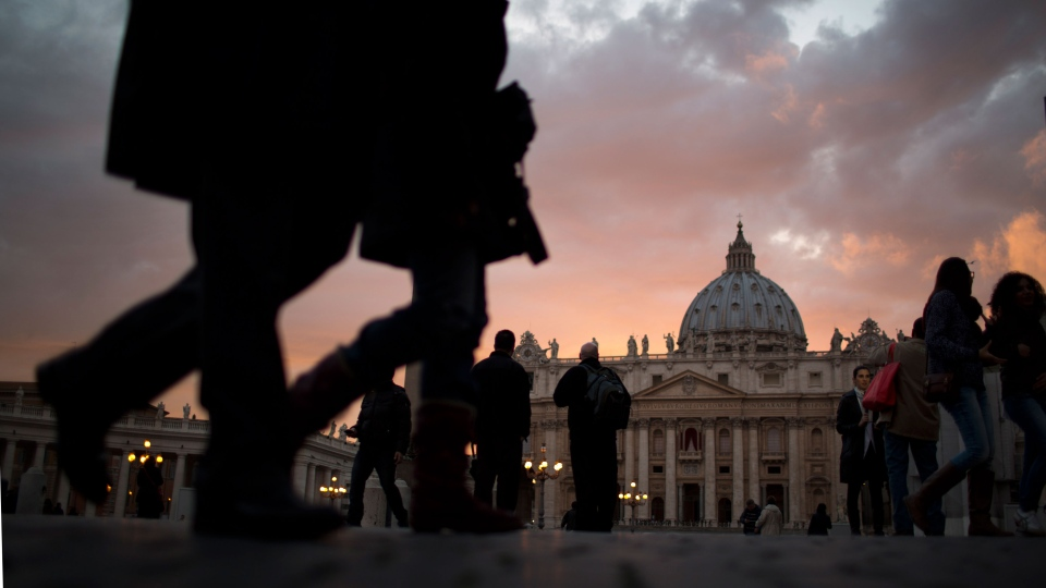 St. Peter's Basilica is seen as people walk outside St. Peter's Square, at the Vatican, Monday, March 11, 2013. (AP / Emilio Morenatti)
