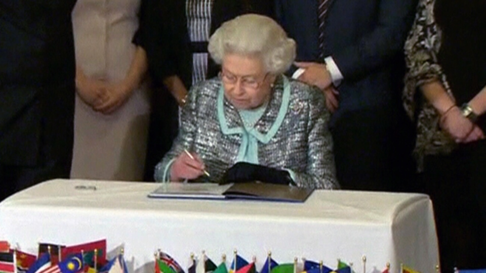 Queen Elizabeth II signs the Commonwealth Charter at a reception at Marlborough House, London, Monday, March 11, 2013.