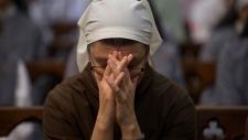 A nun clasps her hands in prayer