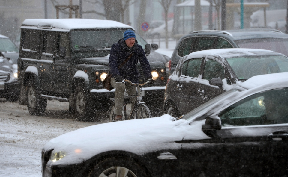 A cyclist and car drivers move across a snow-covered street in Frankfurt, central Germany, Tuesday, March 12, 2013. Winter returned to the German state of Hesse with snow and ice. (AP Photo/dpa, Arne Dedert)