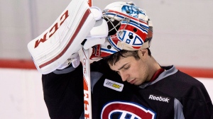 Montreal Canadiens goaltender Carey Price slips on his helmet during their first day of training camp in Brossard, Que., on Sunday, Jan. 13,2013. (Paul Chiasson / THE CANADIAN PRESS)