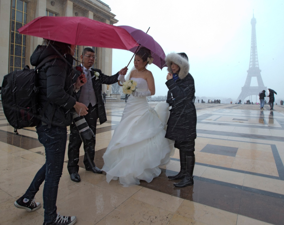 A young newlywed Chinese couple, centre, near the Eiffel Tower in Paris, France, as they talk to photographers for photo sessions in the snow, Tuesday, March 12, 2013. (AP / Jacques Brinon)