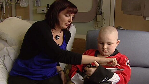 CHEO Child-Life Specialist, Manon Rollin, uses an iPad to walk patient, Justin LeBlanc, through his Cancer surgery