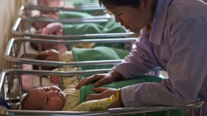 A North Korean nurse comforts a baby at a nursery inside Pyongyang Maternity Hospital in Pyongyang, North Korea on Wednesday, Feb. 20, 2013. (AP Photo/David Guttenfelder)