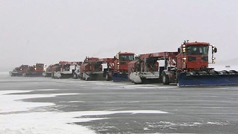 Snow plows work to keep the runways clear at the Ottawa International Airport, Wednesday, Feb. 2, 2011.