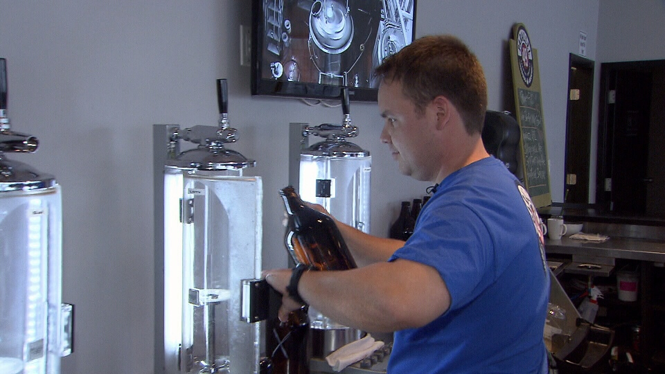 Mike Sleeman of Parallel 49 Brewing Company fills up a growler -- a 64-ounce refillable beer bottle that will soon be subject to a higher tax rate. (CTV)