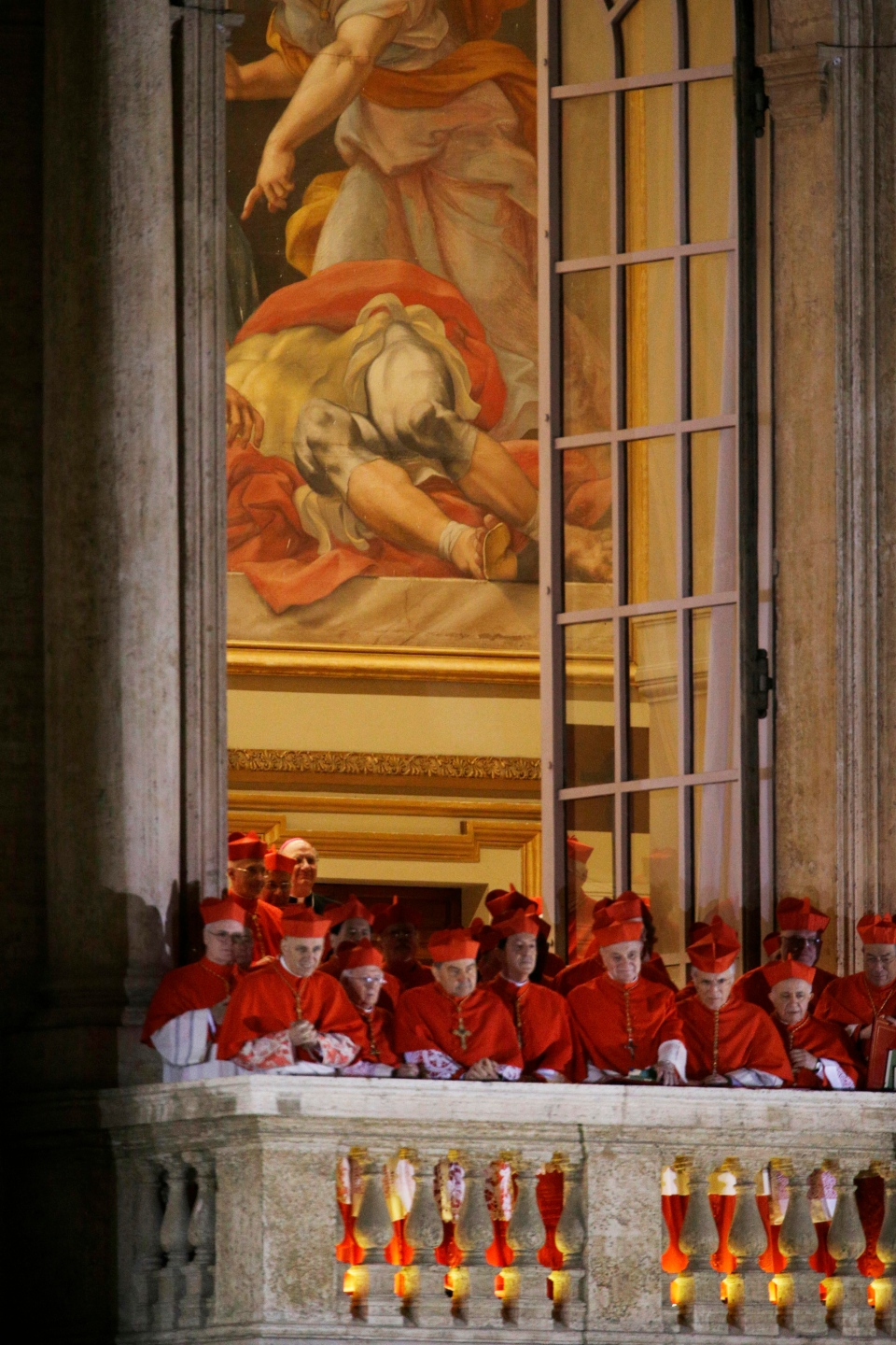 Cardinals watch as Pope Francis speaks to the crowd from the central balcony of St. Peter's Basilica at the Vatican, Wednesday, March 13, 2013. Cardinal Jorge Bergoglio, who chose the name of Francis is the 266th pontiff of the Roman Catholic Church (AP Photo/Andrew Medichini)