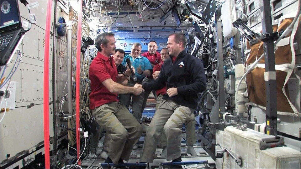 Canadian Astronaut Chris Hadfield shakes hands with American astronaut Kevin Ford after taking over command aboard the International Space Station on Wednesday, March 13, 2013.