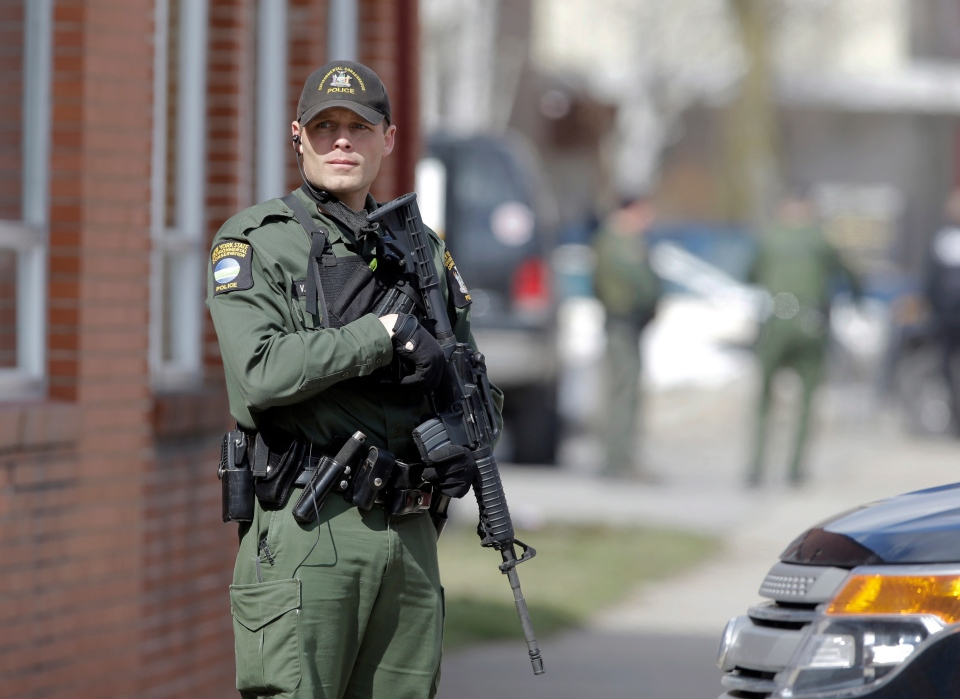 A law enforcement officer stands on Main Street in Herkimer, N.Y., during the search for a suspect in two shootings that killed four and injured at least two on, Wednesday, March 13, 2013. (AP / Mike Groll)