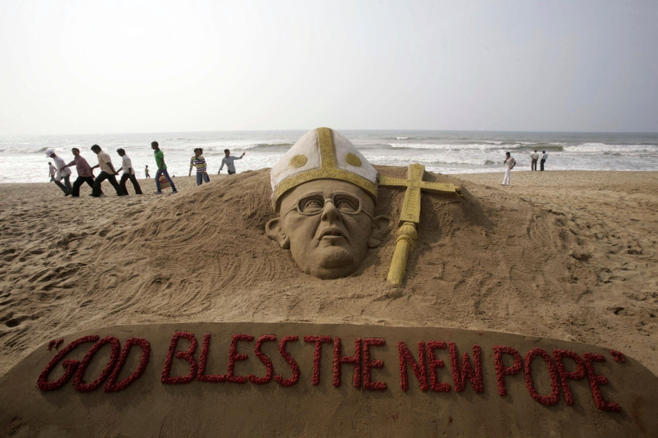 People walk past a sand sculpture of the new pope at the Golden Sea beach on the Bay of Bengal coast in Puri, Orissa state, India, Thursday, March 14, 2013. Jorge Bergoglio of Argentina was elected pope Wednesday, becoming the first pontiff from the Americas. (AP Photo/Biswaranjan Rout)
