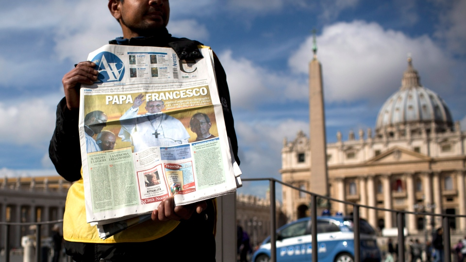 A man sells newspapers with the front page of Pope Francis, in St. Peter's Square at the Vatican, Thursday, March 14, 2013. Argentine Cardinal Jorge Mario Bergoglio, who chose the name of Pope Francis, was elected the 266th pontiff of the Roman Catholic Church on Wednesday, March 13, 2013. (AP / Oded Balilty)