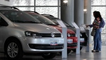 A couple looks at the price of a new vehicle that has already been sold, parked next to other already sold cars on display at a Volkswagen salesroom in Caracas, Venezuela, Feb. 1, 2013. (AP / Ariana Cubillos)