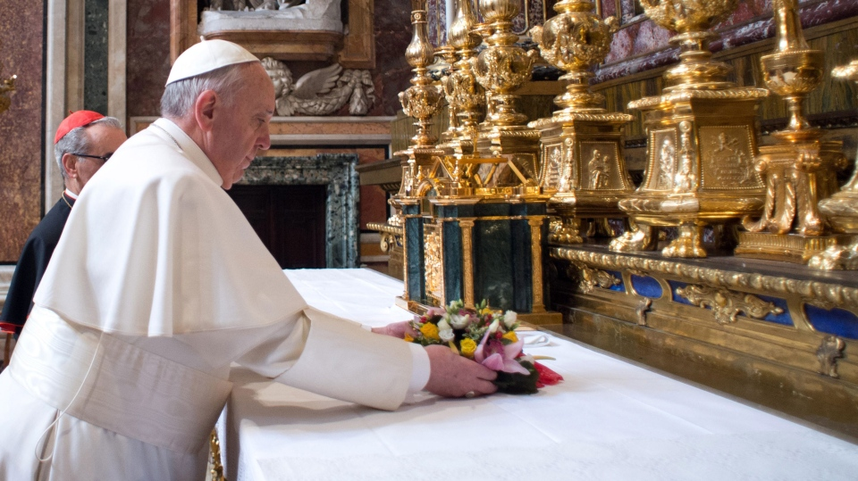 Pope Francis puts flowers on the altar inside St. Mary Major Basilica, in Rome, Thursday, March 14, 2014. (L'Osservatore Romano)