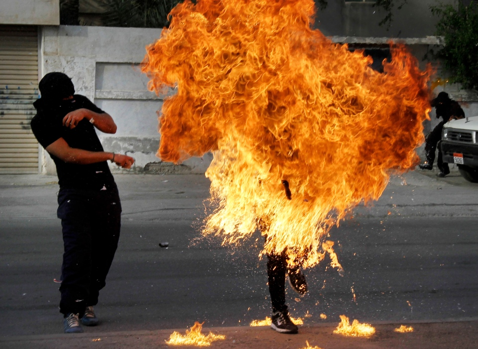 A Bahraini anti-government protester is engulfed in flames when a shot fired by riot police hit the petrol bomb in his hand that he was preparing to throw during clashes in Sanabis, Bahrain, Thursday, March 14, 2013. (AP / Hasan Jamali)