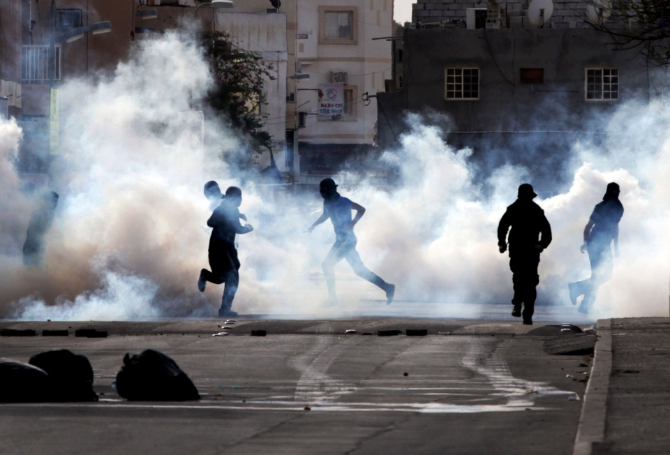 Bahraini anti-government protesters react to tear gas fired by riot police in Sanabis, Bahrain, Thursday, March 14, 2013. (AP / Hasan Jamali)