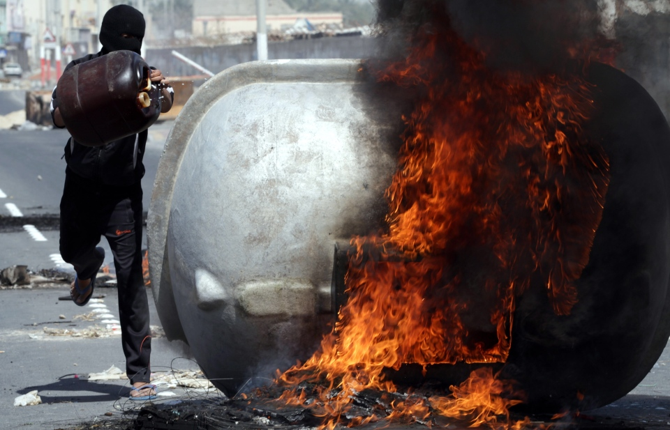 A Bahraini anti-government protester adds fuel to a burning water tank in Malkiya village, Bahrain, Thursday, March 14, 2013. (AP / Hasan Jamali)