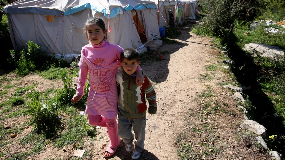 Syrian refugees walk next of their tents at a small refugee camp, in Ketermaya village southeast of Beirut, Lebanon, Thursday March 14, 2013. (AP / Hussein Malla)