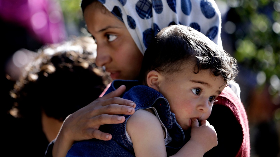 A Syrian refugee girl carries her sister, as she listens to the United Nations High Commissioner for Refugees, UNHCR, chief Antonio Guterres, not seen, during his visit to a Syrian refugee camp, in Ketermaya village southeast of Beirut, Lebanon, Thursday March 14, 2013. (AP / Hussein Malla)