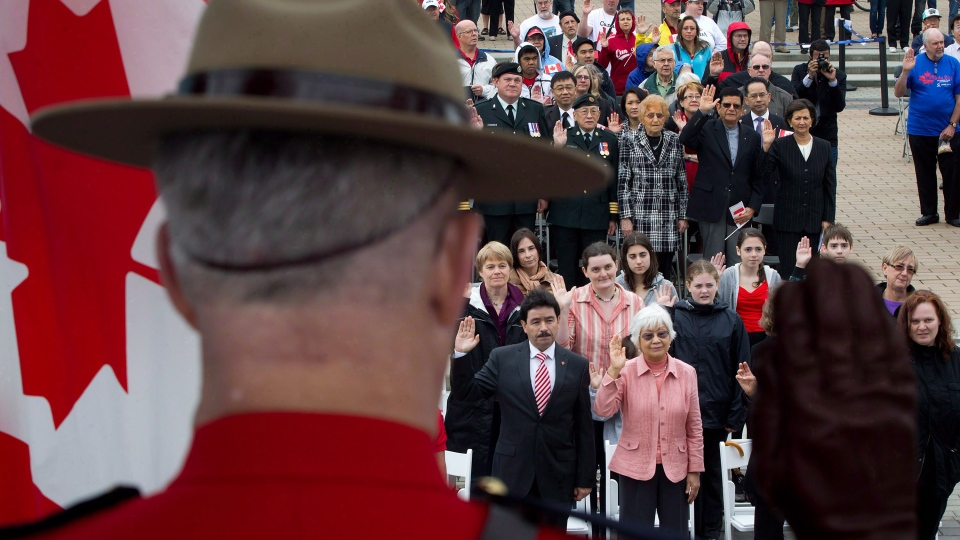An RCMP officer raises his hand as a group of 60 people take the oath of citizenship during a special Canada Day citizenship ceremony in Vancouver, B.C., on Sunday, July 1, 2012. (Darryl Dyck / THE CANADIAN PRESS)