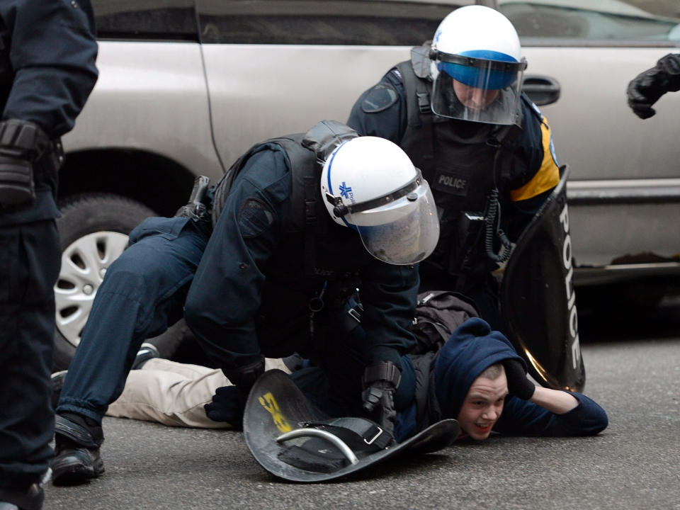 A protester is arrested during an anti-police brutality demonstration in Montreal on Friday, March 15, 2013. (Ryan Remiorz / THE CANADIAN PRESS)