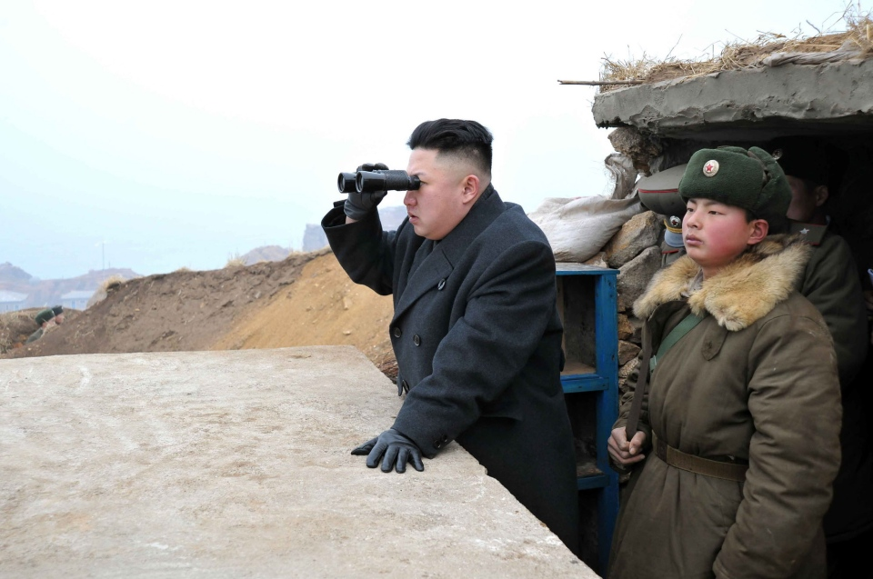 North Korean leader Kim Jong Un, center, uses binoculars to look at the South's territory from an observation post at the military unit on Jangjae islet, located in the southernmost part of the southwestern sector of North Korea's border with South Korea, March 7, 2013. (AP / KCNA via KNS)