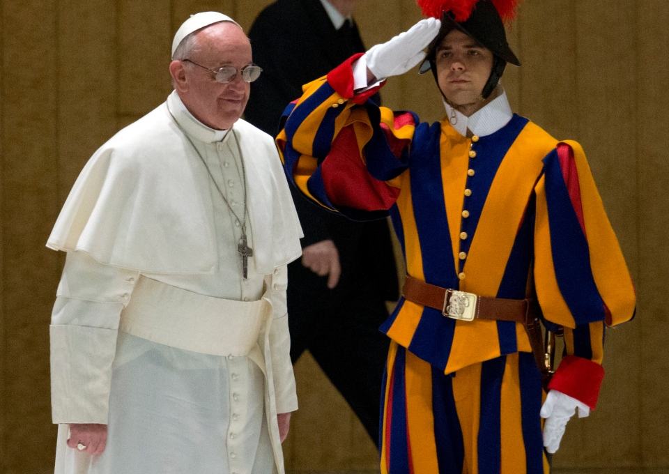 Pope Francis walks past a Swiss guard as he arrives for a meeting with the media at the Pope VI hall, at the Vatican, Saturday, March 16, 2013. (AP / Michael Sohn)