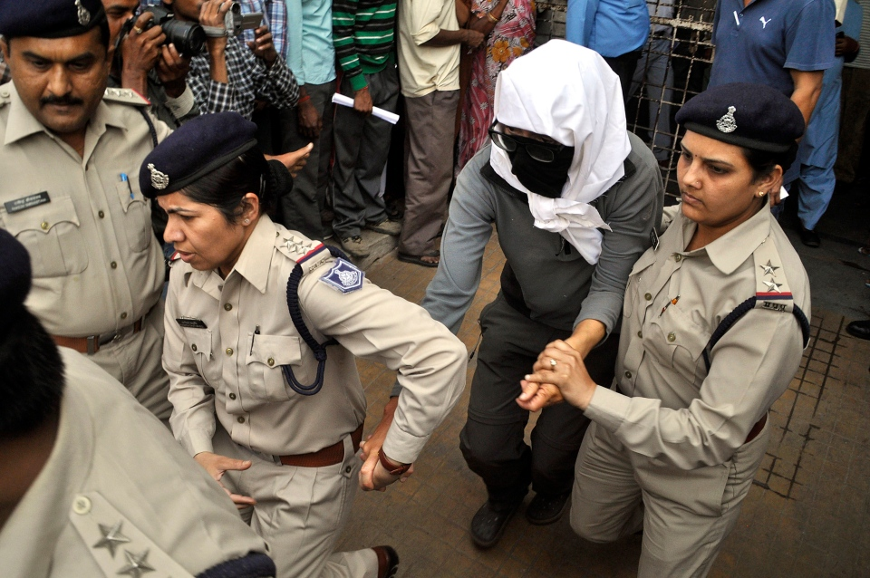 A Swiss woman, centre, who was gang raped by a group of eight men while touring by bicycle with her husband, is escorted by policewomen for a medical examination at a hospital in Gwalior, in the central Indian state of Madhya Pradesh, Saturday, March 16, 2013. (AP Photo)