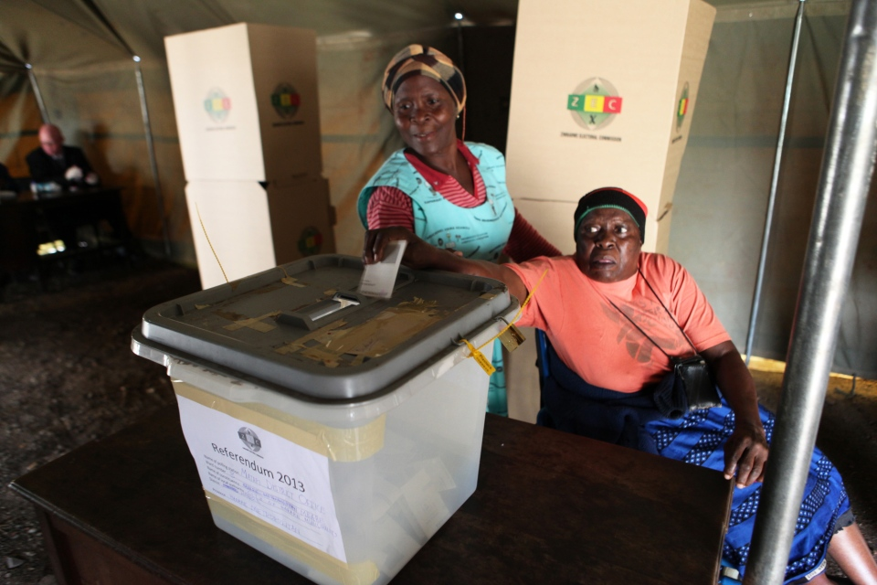A woman is assisted to cast her vote during a referendum in Harare, Zimbabwe, Saturday, March, 16, 2013. (AP / Tsvangirayi Mukwazhi)