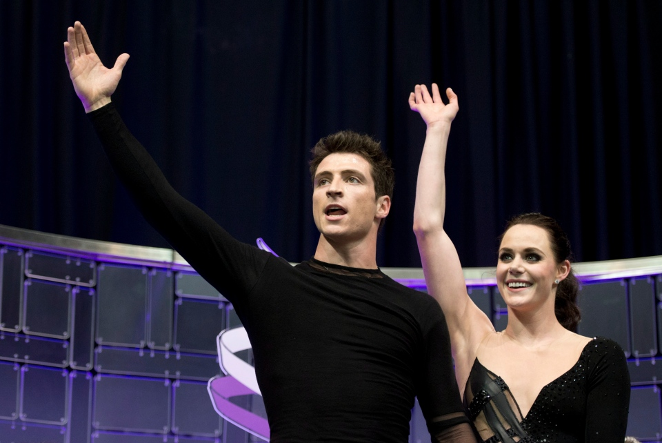 Tessa Virtue and Scott Moir wave to the crowd following their free dance in the ice dance competition at the World Figure Skating Championships in London, Ont., Saturday, March 16, 2013 . (Paul Chiasson / THE CANADIAN PRESS)
