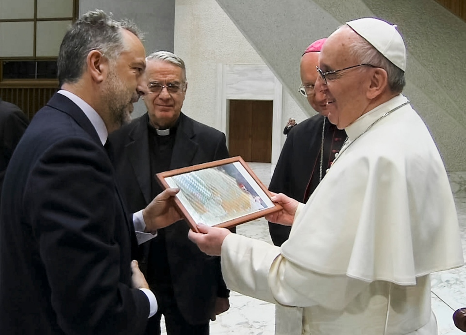 Domenico Stinellis, chief photo editor for The Associated Press in Rome, left, presents Pope Francis with a framed picture taken by AP photographer Luca Bruno on the night of the election, during Pope Francis' audience with journalists in the Paul VI Hall at the Vatican, Saturday, March 16, 2013. (AP / CTV)