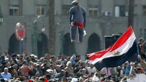 Egyptian protesters wave Egyptian flags under an effigy representing a hanged President Mubarak during a protest in Tahrir square in Cairo, Egypt, Friday, Feb. 4, 2011. (AP / Lefteris Pitarakis)