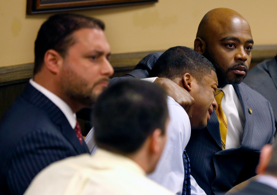 Defense attorney Walter Madison, right, holds his client, 16-year-old Ma'lik Richmond, second from right, while defense attorney Adam Nemann, left, sits with his client Trent Mays, foreground, 17, as Judge Thomas Lipps pronounces them both delinquent on rape and other charges after their trial in juvenile court in Steubenville, Ohio on Sunday, March 17, 2013. (AP / Keith Srakocic)