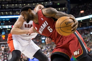 Miami Heat's LeBron James drives past Toronto Raptors' Jonas Valanciunas during first half NBA basketball action in Toronto on Sunday, March 17, 2013. THE CANADIAN PRESS/Chris Young
