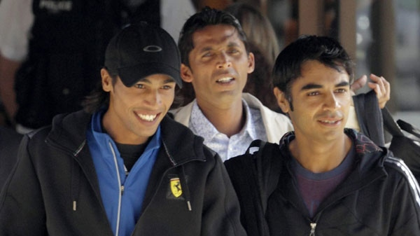 In this Wednesday, Sept. 1, 2010 file photo Pakistan cricket players Mohammad Amir, left, Salman Butt, right, and Mohammad Asif, centre rear, walk to a taxi flanked by security men, as they leave their hotel in Taunton, England.