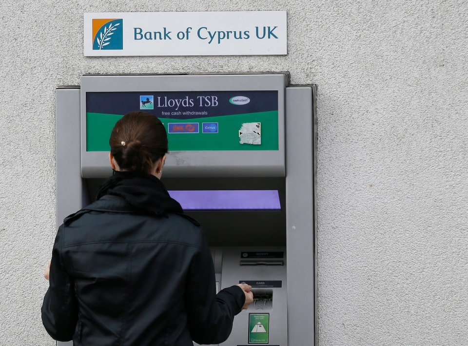 A woman uses a bank of Cyprus U.K. branch cash machine in London on Monday, March, 18, 2013. (AP / Alastair Grant)