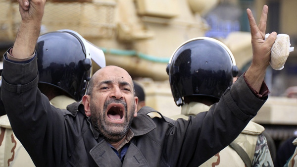 An Egyptian anti-Mubarak protester flashes the V sign in front of a tank in Tahrir square in Cairo, Egypt, Saturday, Feb. 5, 2011. (AP Photo/Amr Nabil)