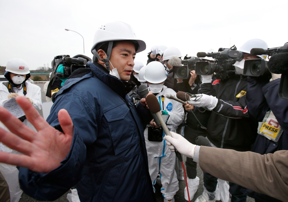 Senior Vice-Minister of Environment Shinji Inoue answers a reporter's question after inspecting workers' decontamination operation at the entrance of the Joban Expressway in Tomioka, Fukushima prefecture inside the exclusion zone surrounding the Fukushima Dai-ichi nuclear plant in Japan, Friday, March 1, 2013. (AP / Shizuo Kambayashi)