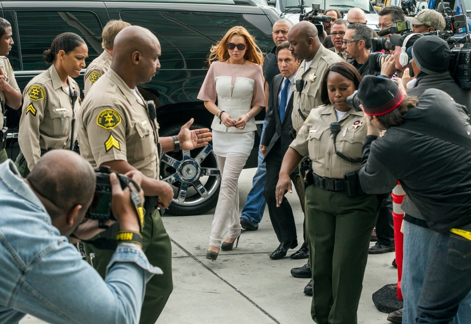 Actress Lindsay Lohan walks with her attorney Mark Heller, after attending a trial at a Los Angeles Superior court on Monday, March 18, 2013.  (AP / Damian Dovarganes)
