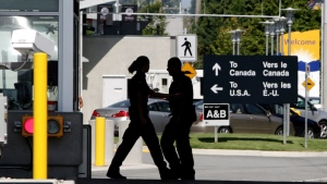 Canadian border guards are silhouetted as they replace each other at an inspection booth at the Douglas border crossing on the Canada-USA border in Surrey, B.C. (Darryl Dyck / THE CANADIAN PRESS)