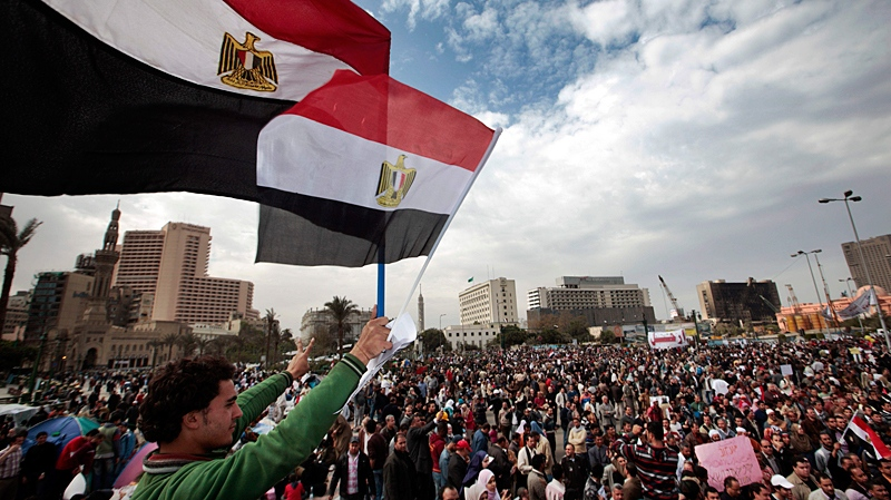 An Egyptian anti-government demonstrator waves national flags as thousands gather in Tahrir Square, the center of anti-government demonstrations, in Cairo, Egypt, Sunday, Feb. 6, 2011. (AP / Lefteris Pitarakis)