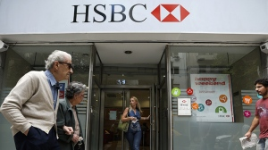 People walk in front of an HSBC branch in Buenos Aires, Argentina, Monday, March 18, 2013. (AP Photo / Victor R. Caivano)