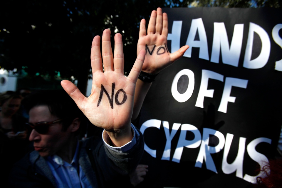 Protesters hold up their hands as they protest outside the parliament in capital Nicosia, Cyprus, Monday, March 18, 2013. (AP / Petros Karadjias)