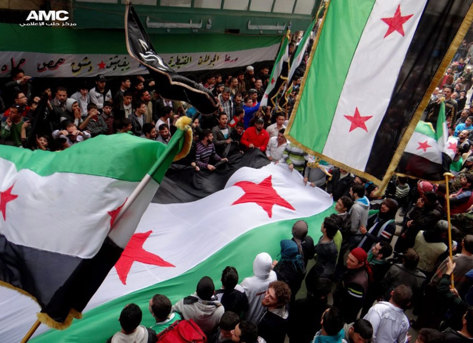 Anti-Syrian regime protesters, wave the Syrian revolutionary flags during a protest to mark the second anniversary of the their uprising, in Aleppo, Syria, Friday March 15, 2013.  (Aleppo Media Center / AMC)